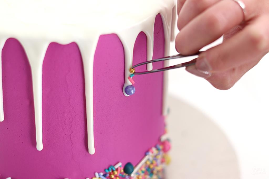 adding sprinkles to drip cake