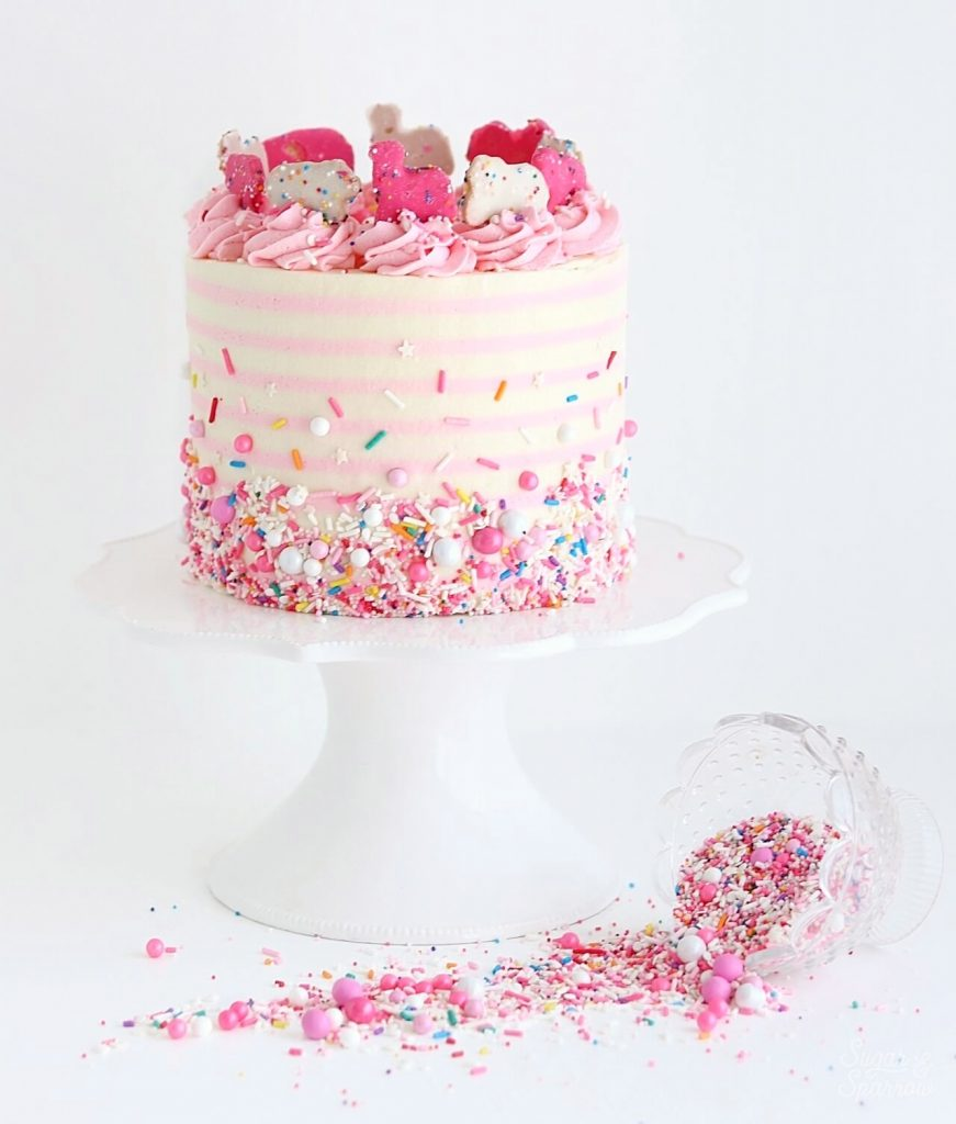 pink and white striped cake with sprinkles