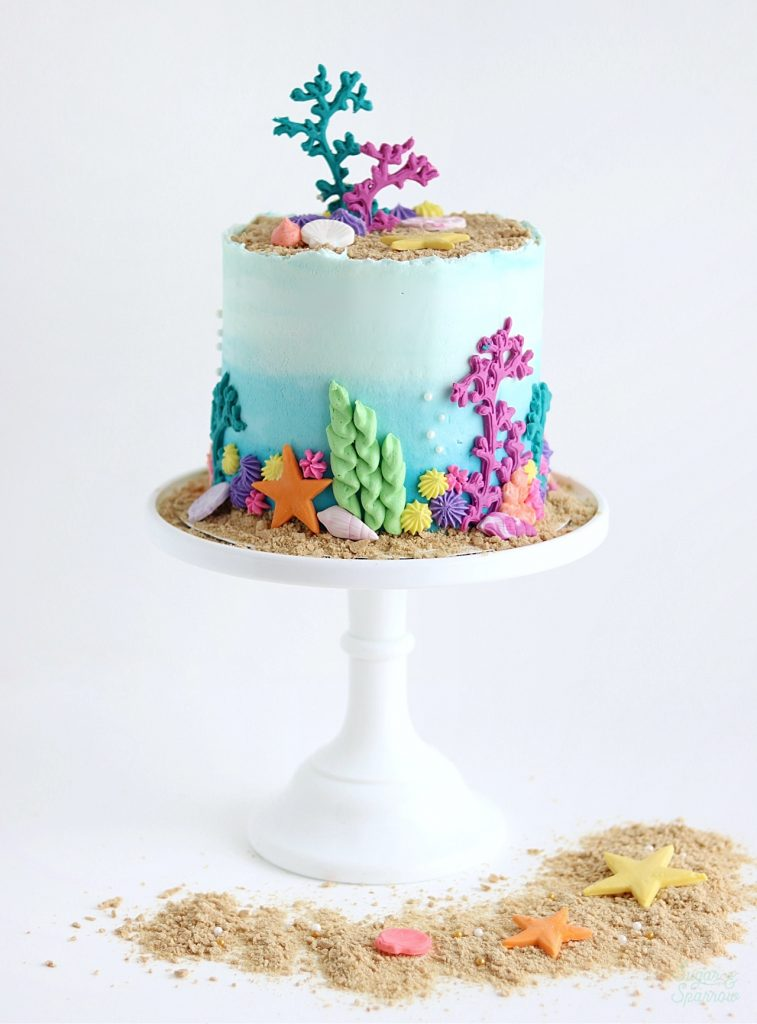blue ombre cake with seashells and sand