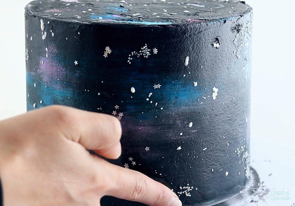 adding sprinkle stars to galaxy cake
