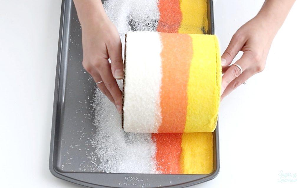 rolling a cake in sugar sprinkles