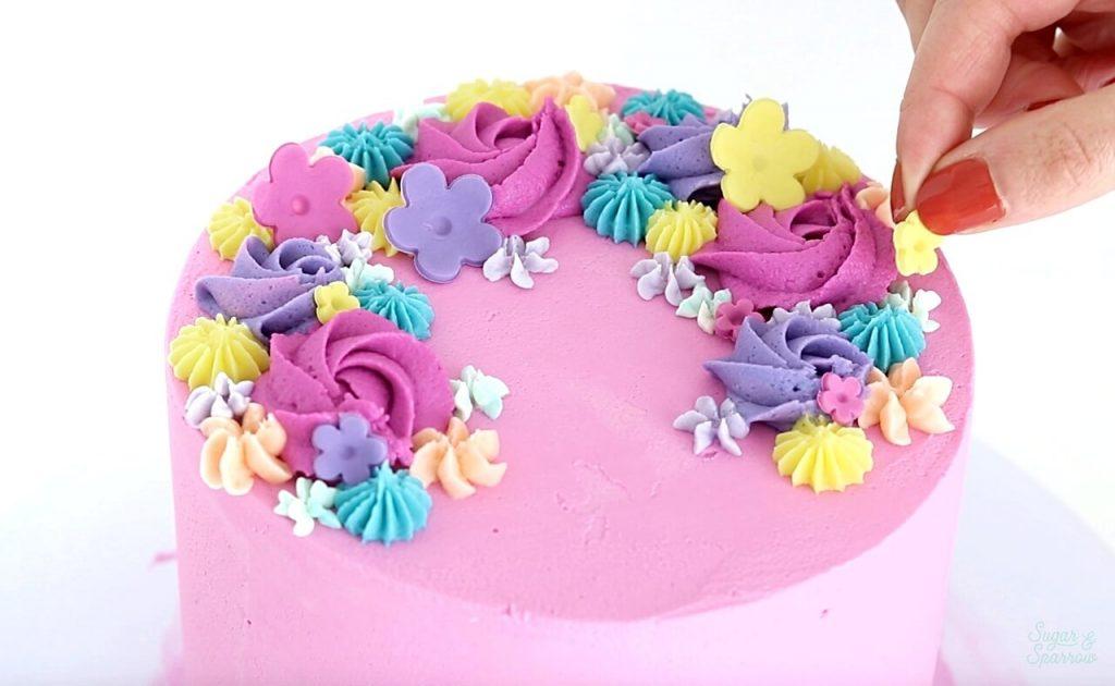 adding fondant flowers to cake