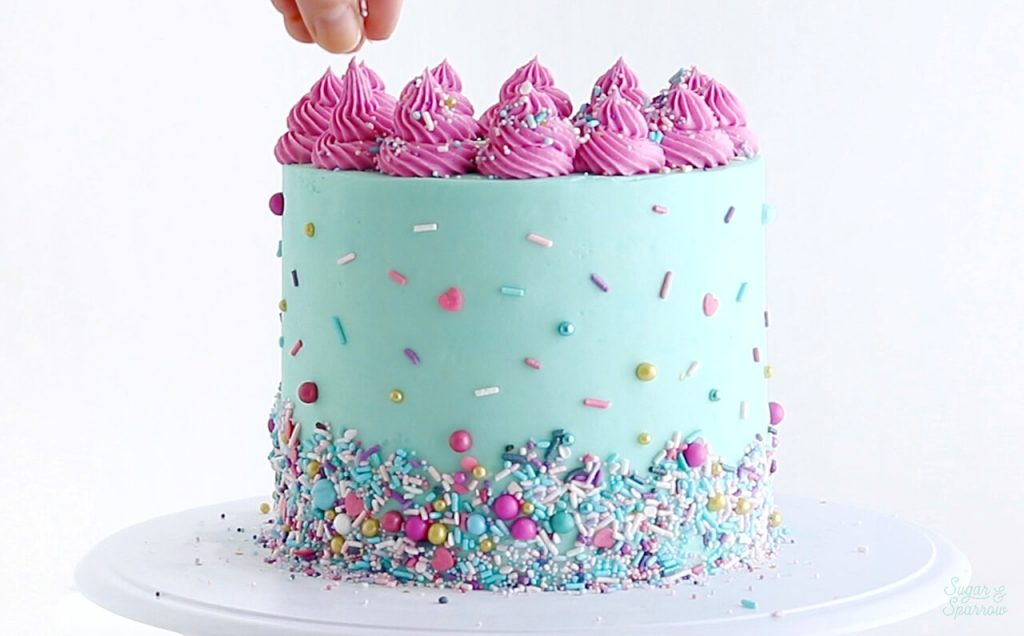 decorating a cake with sprinkles