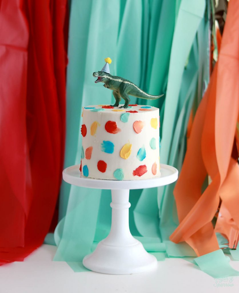 first birthday cake with dinosaur topper by sugar and sparrow